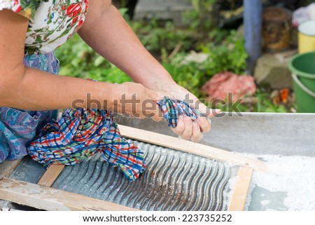 grandmother wash clothes in a tub hands - stock photo