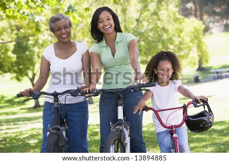 Grandmother with adult daughter and grandchild riding bikes - stock photo