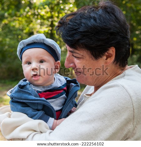 Grandmother with baby smiling outdoors - stock photo