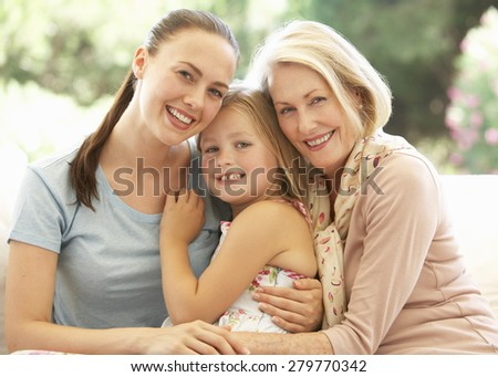 Grandmother With Daughter and Granddaughter Laughing Together On Sofa
