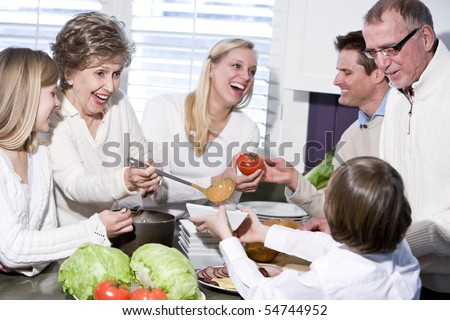 Grandmother with family cooking in kitchen, smiling and laughing together - stock photo