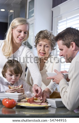 Grandmother with family eating lunch in kitchen - stock photo