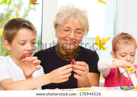 Grandmother with grandchildren applying a dry maple leaves using glue while doing arts and crafts - stock photo