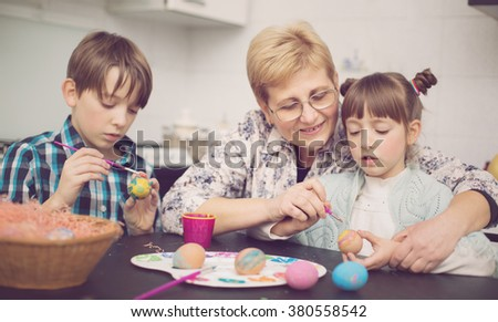 Grandmother with grandchildren are coloring eggs for Easter,  - stock photo