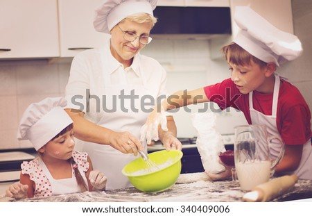Grandmother with grandchildren baking cookies prepare dough - stock photo
