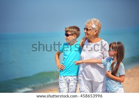Grandmother with grandchildren having fun together on the seaside - stock photo