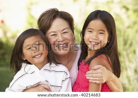 Grandmother With Grandchildren In Garden - stock photo