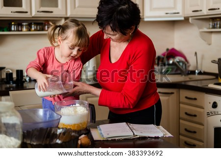 Grandmother with granddaughter baking together cookies, child is pouring milk