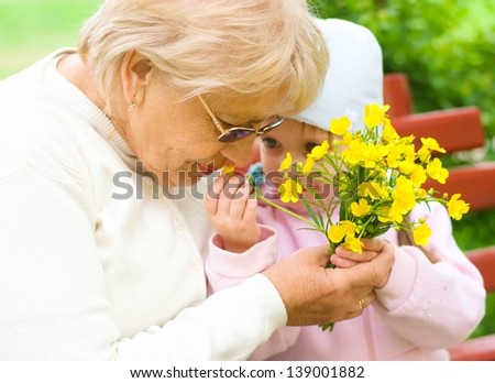 Grandmother with granddaughter sniffing yellow flowers in the park - stock photo