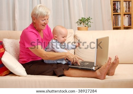 Grandmother with Grandson with laptop - stock photo