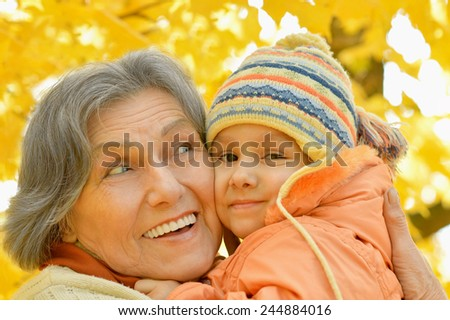 Grandmother with her granddaughter for a walk during the fall of the leaves in the park - stock photo