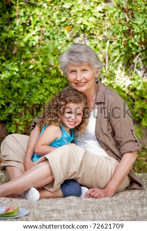 Grandmother with her granddaughter in the garden - stock photo