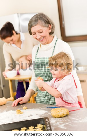 Grandmother with little girl prepare dough for baking in kitchen - stock photo