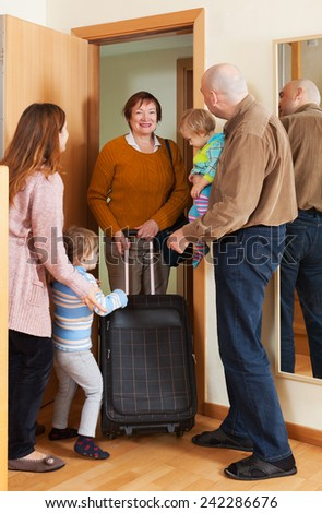 Grandmother with luggage coming to family with children - stock photo