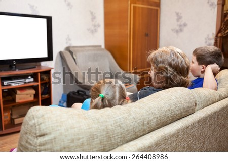 Grandmother with two young kids sitting on couch and watching tv at home, isolated white screen