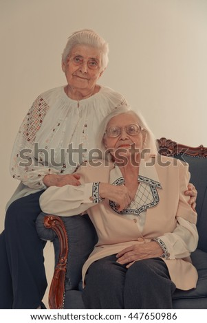 Grandmothers. Two grandmothers sitting in the chair. Two sisters sitting in the chair