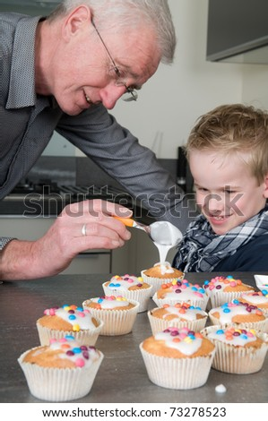 Grandpa and child are decorating the just baked cupcakes - stock photo