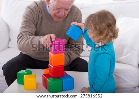 Grandpa and child playing with color cubes - stock photo