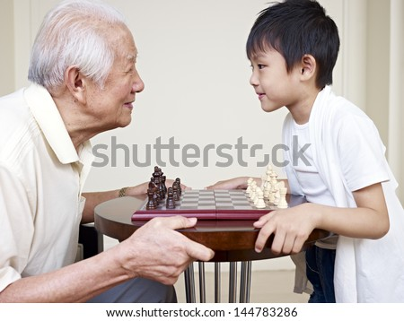 grandpa and grandson looking into each other's eyes before a chess game. - stock photo