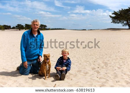 Grandpa and grandson with the dog in nature landscape - stock photo