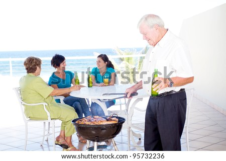 grandpa doing barbecue for the family on balcony - stock photo