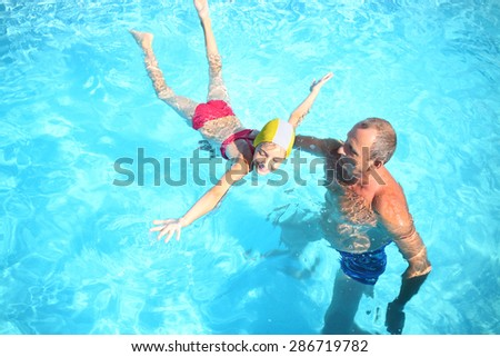 Grandpa teaches granddaughter to swim in the swimming pool, view from the top - stock photo