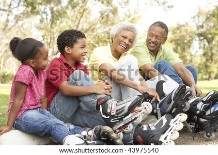 Grandparent With Grandchildren Putting On In Line Skates In Park - stock photo