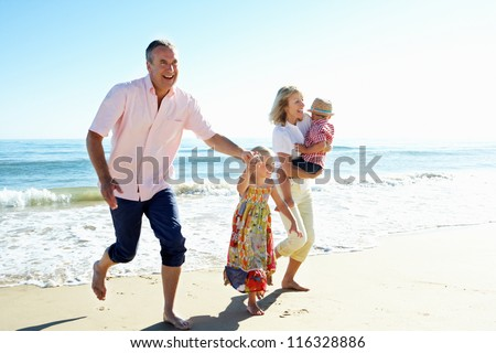Grandparents And Grandchildren Enjoying Beach Holiday - stock photo