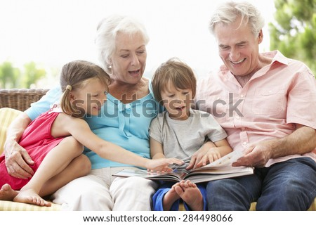 Grandparents And Grandchildren Reading Book On Garden Seat - stock photo