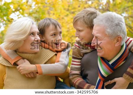 Grandparents and grandchildren together in autumn park - stock photo
