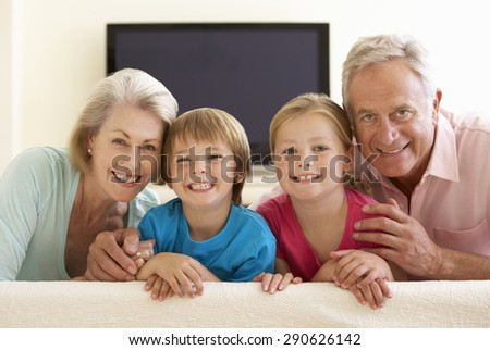 Grandparents And Grandchildren Watching Widescreen TV At Home