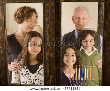 grandparents and grandchildren with Hanukkia, at the window - stock photo