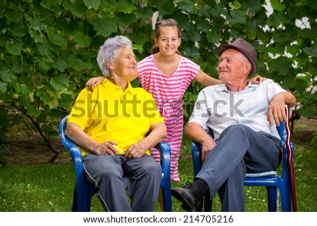 Grandparents and granddaughter  sitting outside
