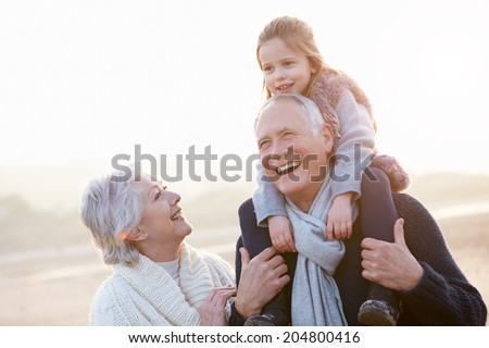 Grandparents And Granddaughter Walking On Winter Beach - stock photo
