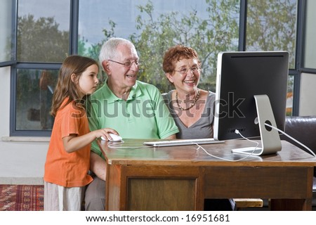 grandparents and granddaughter with computer at home - stock photo