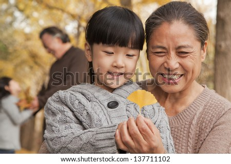 Grandparents and granddaughters in park - stock photo