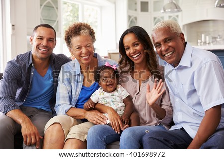 Grandparents and parents with a baby girl on mumâ??s knee - stock photo