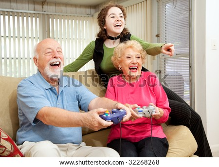 Grandparents and teen girl having fun playing video games. - stock photo