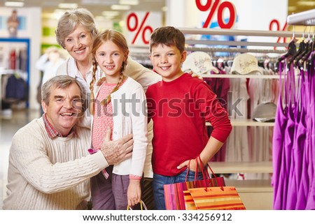 Grandparents and their grandchildren looking at camera in one of departments of mall - stock photo