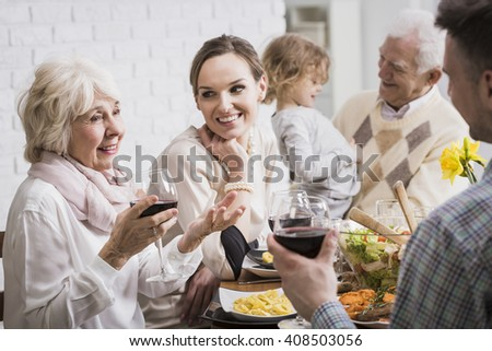 Grandparents, granddaughter and young married couple sitting beside table during dinner - stock photo