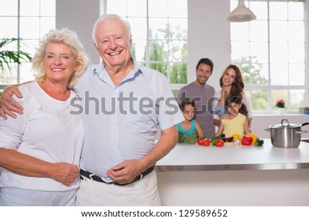 Grandparents in front of their family in the kitchen - stock photo