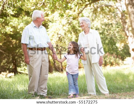 Grandparents In Park With Granddaughter - stock photo