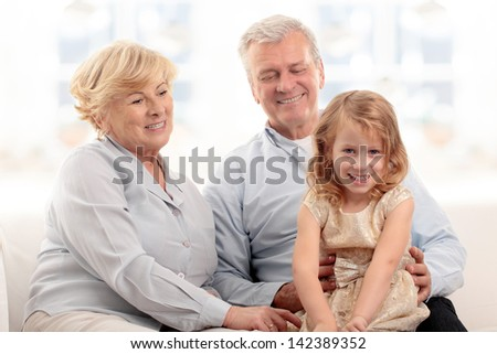 Grandparents laughing with granddaughter on couch at home - stock photo