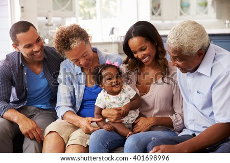 Grandparents, parents and a happy baby girl on mumâ??s knee - stock photo