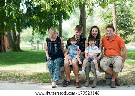 Grandparents, parents and children are sitting on the bench, outside in the park. - stock photo