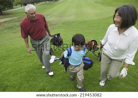 Grandparents playing golf with grandson - stock photo