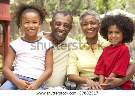 Grandparents Relaxing In Garden With Grandchildren - stock photo