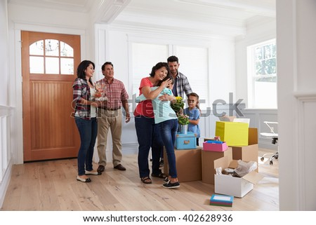 Grandparents Visiting Hispanic Family In New Home - stock photo