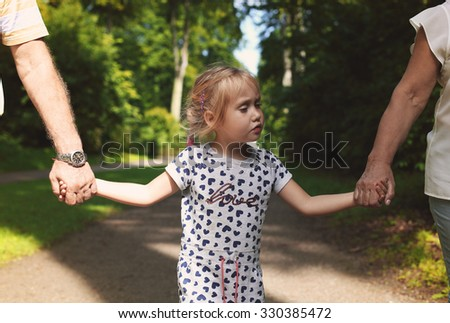 Grandparents With Grandchild walking together in the park - stock photo