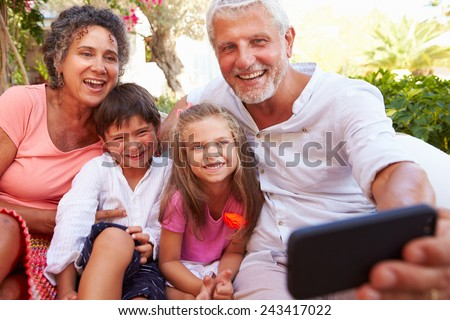 Grandparents With Grandchildren In Garden Taking Selfie - stock photo